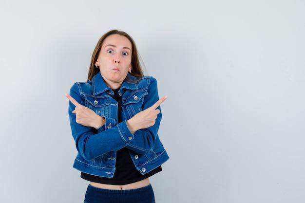 Jonge dame wijst weg terwijl ze haar blouse, jas en jas ophaalt en er verward uitziet. vooraanzicht.