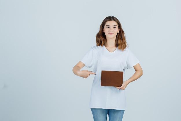 Jonge dame wijzend boek in t-shirt, spijkerbroek en op zoek zelfverzekerd. vooraanzicht.