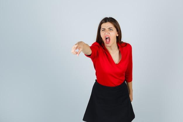 Jonge dame wijzend met wijsvinger in rode blouse