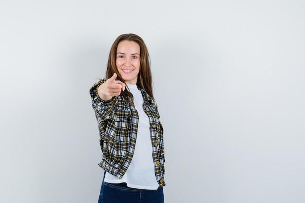 Jonge dame wijzend op camera in t-shirt, jasje, spijkerbroek en op zoek gelukkig, vooraanzicht.