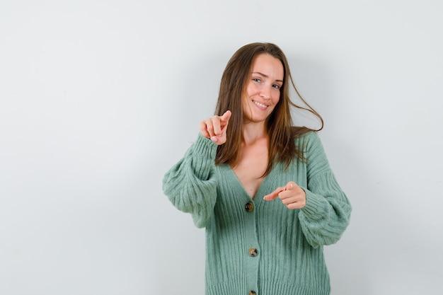 Jonge dame wijzend op camera in wollen vest en kijkt zelfverzekerd. vooraanzicht.