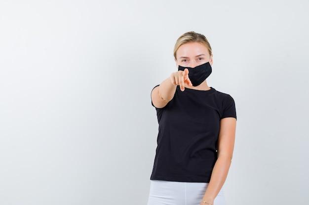 Jonge dame wijzend op camera in zwart t-shirt, masker en op zoek zelfverzekerd. vooraanzicht.