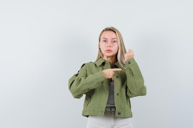 Jonge dame wijzend op de mouw van haar jas in jas, broek en op zoek verstandig, vooraanzicht. Gratis Foto
