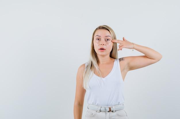 Jonge dame wijzend op haar oog in witte blouse en op zoek naar gerichte ruimte voor tekst