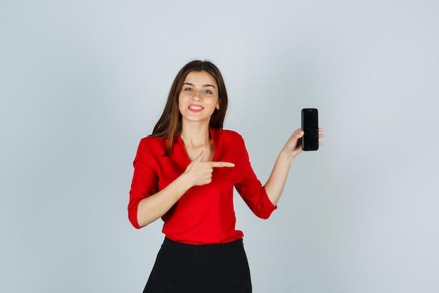 Jonge dame wijzend op mobiele telefoon in rode blouse, rok en op zoek vrolijk