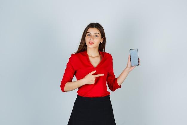 Jonge dame wijzend op mobiele telefoon in rode blouse, rok en op zoek zelfverzekerd
