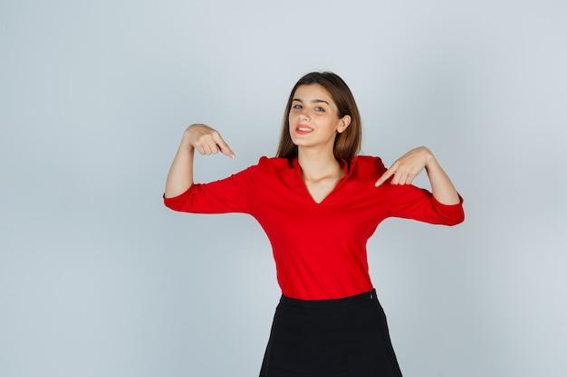 Jonge dame wijzend op zichzelf in rode blouse, rok en op zoek trots