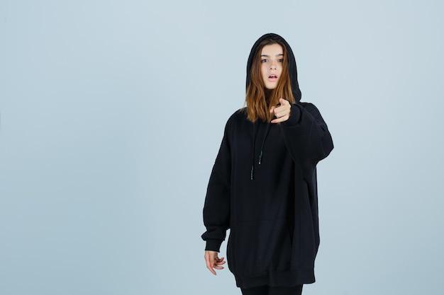 Jonge dame wijzende camera in oversized hoodie, broek en kijkt verbaasd. vooraanzicht.