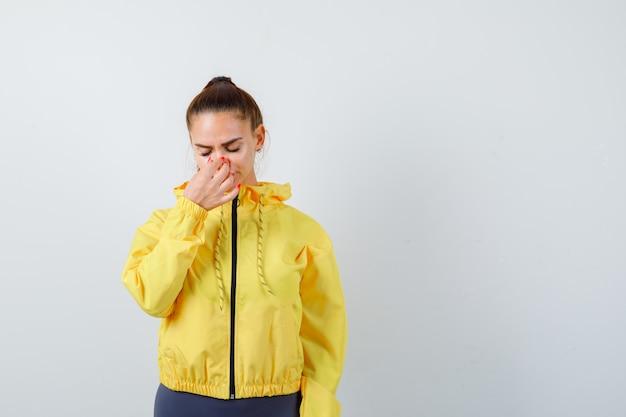 Jonge dame wrijft over haar neus in gele jas en ziet er moe uit, vooraanzicht.