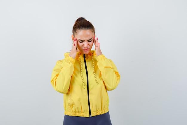 Jonge dame wrijft over haar slapen in een gele jas en ziet er pijnlijk uit, vooraanzicht.