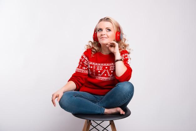 Jonge dame zittend op een stoel luisteren naar de muziek en wegkijken in de buurt van een witte muur