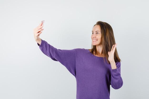 Jonge dame zwaaiende hand op videocall in violet overhemd en op zoek blij. vooraanzicht.