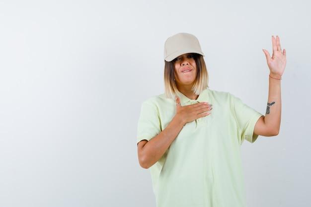 Jonge dame zwaaiende hand voor groet in t-shirt, pet en aarzelend, vooraanzicht op zoek.