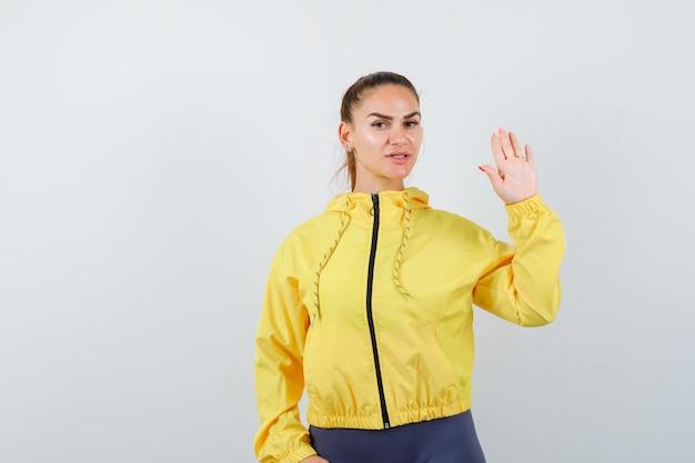 Jonge dame zwaait met de hand om afscheid te nemen in gele jas en ziet er zelfverzekerd uit. vooraanzicht.