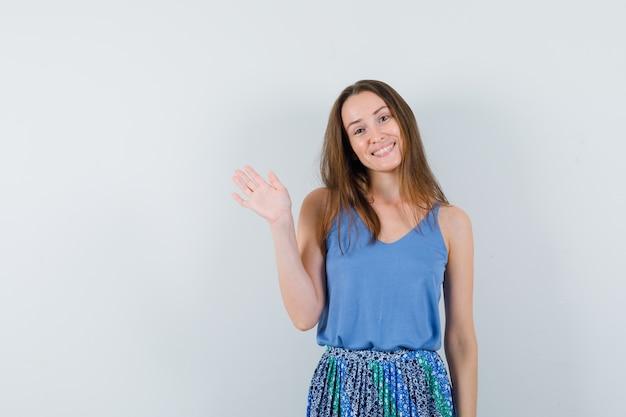 Jonge dame zwaait met de hand om afscheid te nemen in hemd, rok en op zoek vrolijk, vooraanzicht.