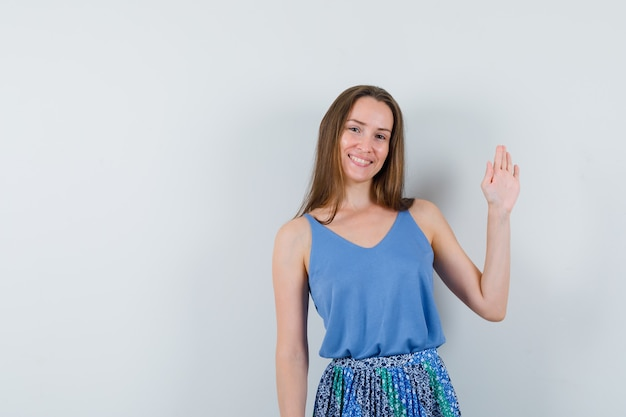 Jonge dame zwaait met de hand om afscheid te nemen in hemd, rok en ziet er vrolijk uit, vooraanzicht.