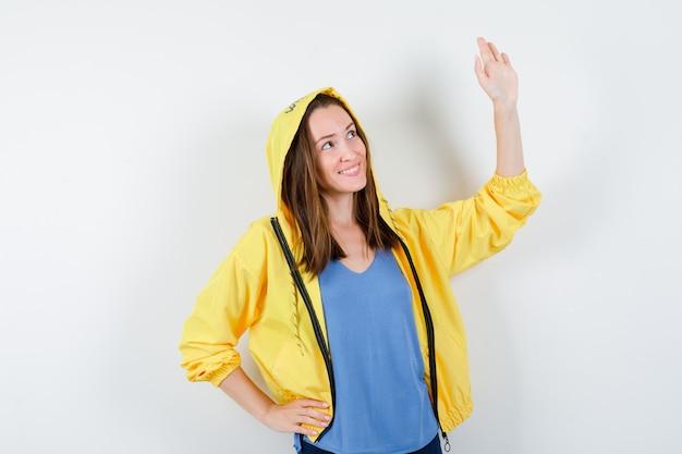 Jonge dame zwaait met de hand om afscheid te nemen in t-shirt, jas en ziet er vrolijk uit, vooraanzicht.