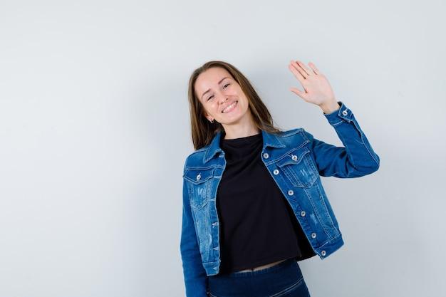 Jonge dame zwaait met de hand voor begroeting in blouse, jas en ziet er vrolijk uit Gratis Foto