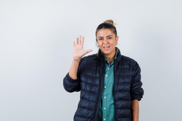 Jonge dame zwaait met de hand voor begroeting in shirt, pufferjack en ziet er vrolijk uit, vooraanzicht.