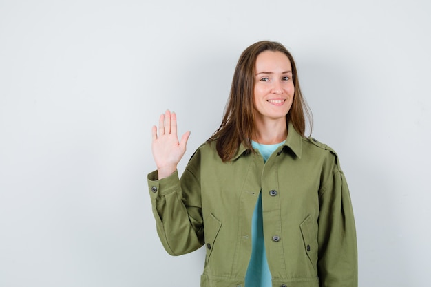 Jonge dame zwaait met de hand voor begroeting in t-shirt, jas en ziet er schattig uit. vooraanzicht.