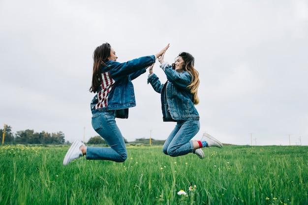 Jonge dames hebben plezier in het veld en handen klappen