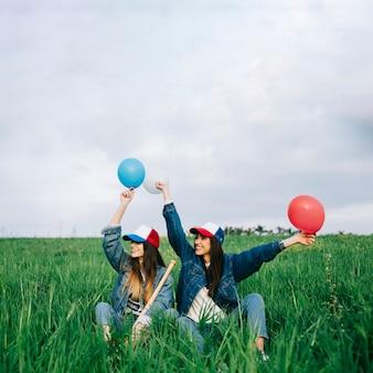 Jonge dames met plezier in de zomer veld met verschillende kleuren ballen
