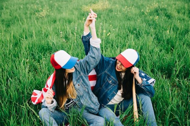 Jonge dames zittend op groen gras en hand in hand
