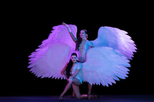 Jonge danseres met engel vleugels in neonlicht op zwarte muur