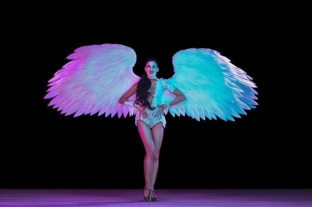 Jonge danseres met engelenvleugels in neonlicht op zwarte muur