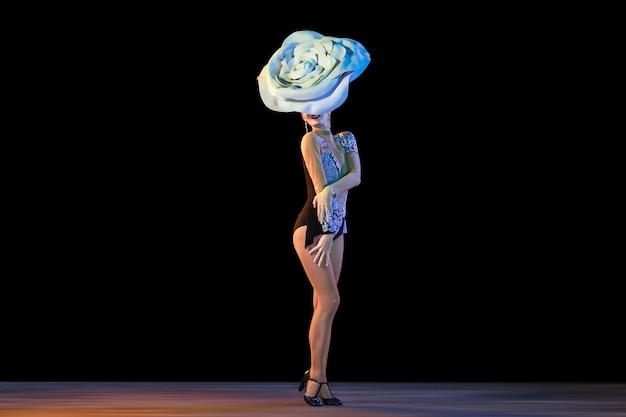 Jonge danseres met enorme bloemenhoed in neonlicht op zwarte muur