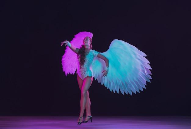 Jonge danseres met witte engelenvleugels in paars blauw neonlicht op zwarte muur.