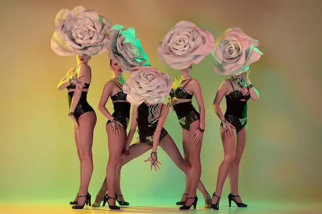 Jonge danseressen met enorme bloemenhoeden in neonlicht op gradiëntmuur
