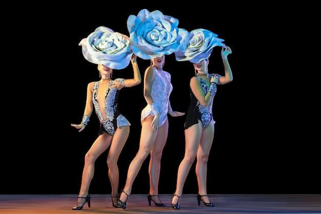 Jonge danseressen met enorme bloemenhoeden in neonlicht op zwarte muur