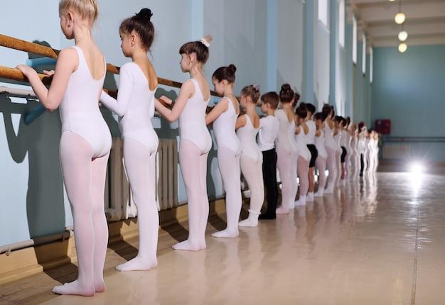 Jonge dansers in de balletstudio. jonge dansers voeren gymnastiekoefeningen in het ballet of de barre uit tijdens een warming-up in de klas.