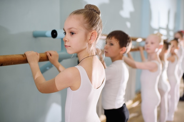 Jonge dansers in de balletstudio. jonge dansers voeren gymnastische oefeningen uit in het ballet of de barre terwijl ze opwarmen in de klas.