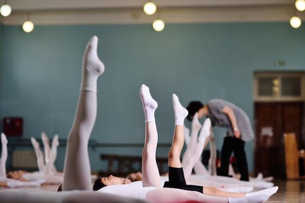 Jonge dansers in de balletstudio. jonge dansers voeren gymnastische oefeningen uit tijdens een warming-up in de klas. sport, gymnastiek, ontwikkeling van kinderen