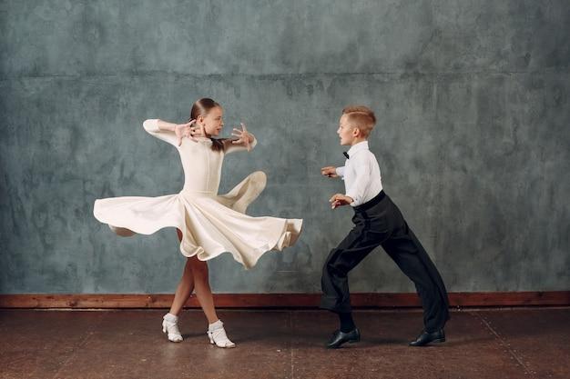Jonge dansersjongen en meisje die in stijldans samba dansen