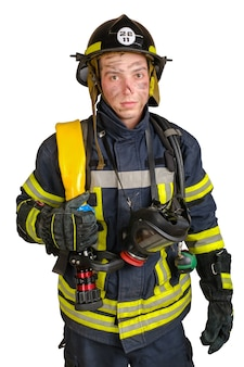Jonge dappere man in uniform en veiligheidshelm van brandweerman met brandslang