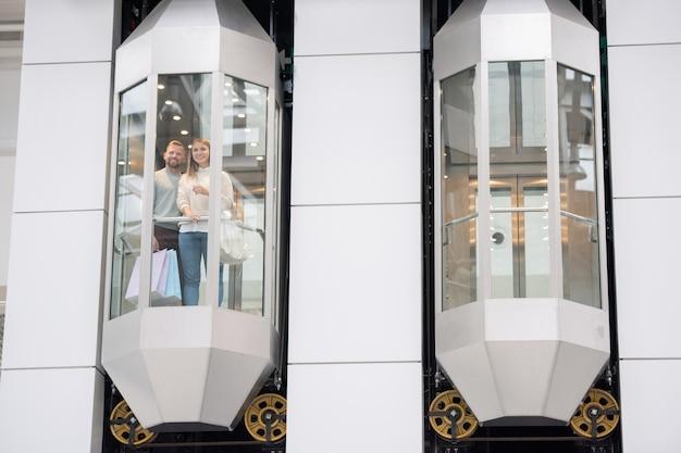 Jonge dates staan in een van de liften en kijken door het raam terwijl ze genieten van winkelen in het winkelcentrum op zwarte vrijdag