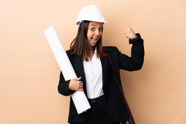 Jonge de holdingsblauwdrukken van de architectenvrouw over geïsoleerd doend sterk gebaar
