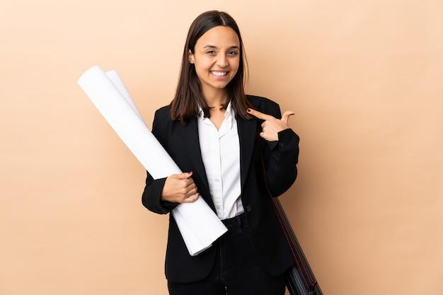Jonge de holdingsblauwdrukken van de architectenvrouw over muur geven duimen omhoog gebaar
