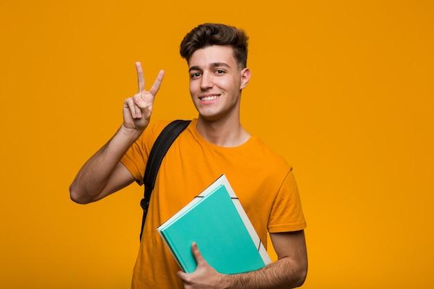 Jonge de holdingsboeken die van de studentenmens zijdelings met twijfelachtige en sceptische uitdrukking kijken.