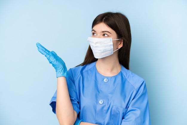 Jonge de holdingshulpmiddelen van de tandartsvrouw over blauwe muur