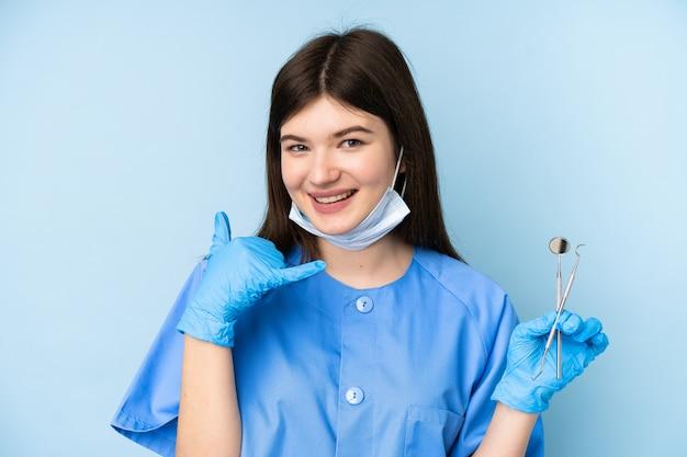 Jonge de holdingshulpmiddelen van de tandartsvrouw over geïsoleerde blauwe muur die telefoongebaar maken