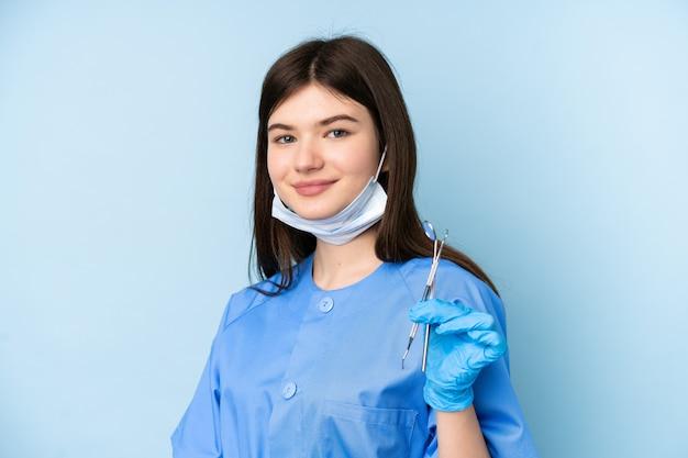 Jonge de holdingshulpmiddelen van de tandartsvrouw over het geïsoleerde blauwe muur lachen