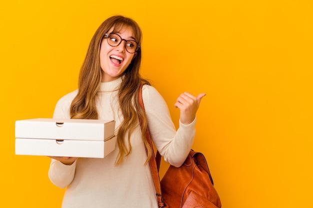 Jonge de holdingspizza's van de studenten kaukasische vrouw over geïsoleerde muurpunten met duimvinger weg, lachend en zorgeloos