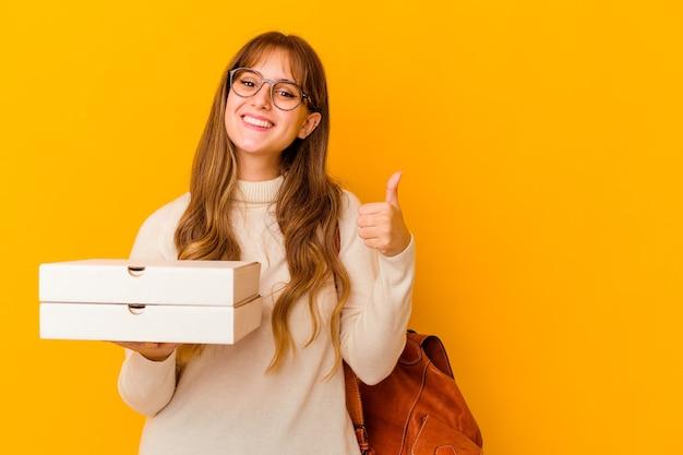 Jonge de holdingspizza's van de studentenvrouw over geïsoleerde muur die en duim glimlachen opheffen