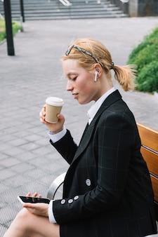 Jonge de koffiekop die van de onderneemsterholding mobiele telefoon bekijken