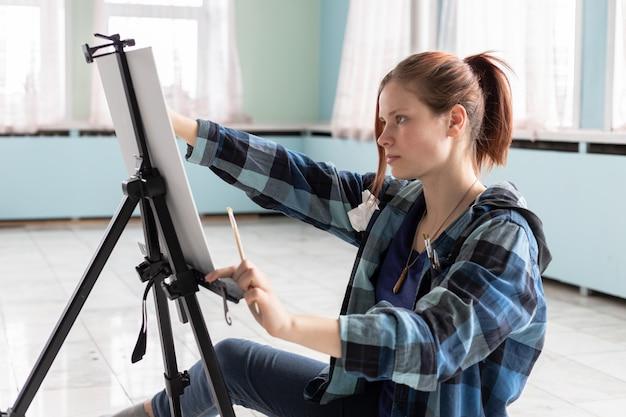 Jonge de kunstenaarsverven van de tienervrouw met olieverven die op de marmeren vloer zitten. wit canvas en ezel staan op de vloer van marmeren tegels in de kamer met turquoise en lichtgroene muren.