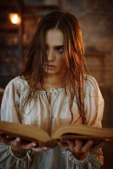 Jonge demonische vrouw houdt boek met spreuken, demonen uitdrijven. exorcisme, mysterie, paranormaal ritueel, duistere religie, nachthorror, drankjes op de plank